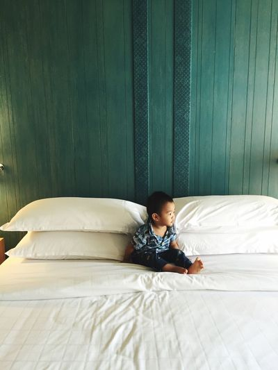 High Angle View Of Baby Boy Sitting On Bed At Home