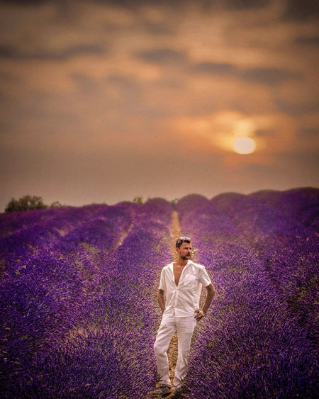 Full length of mid adult man standing on field amidst flowers against cloudy sky during sunset