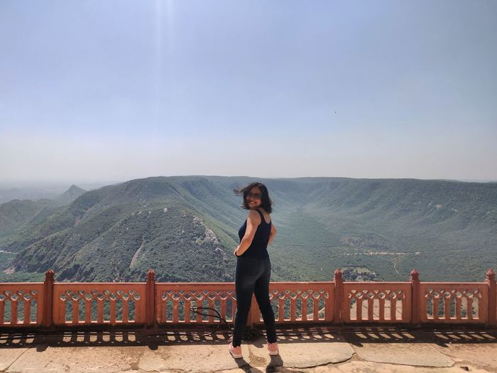 Full length of woman standing on railing against mountains