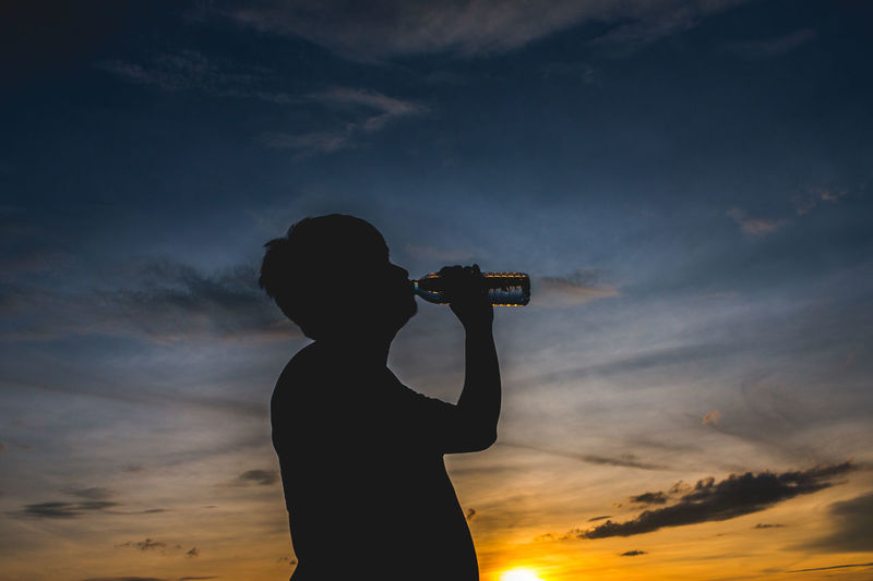 Silhouette man drinking water against sky during sunset