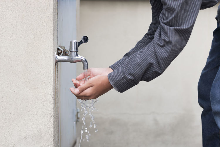 Close-Up Of Hands Holding Water Running From Tap