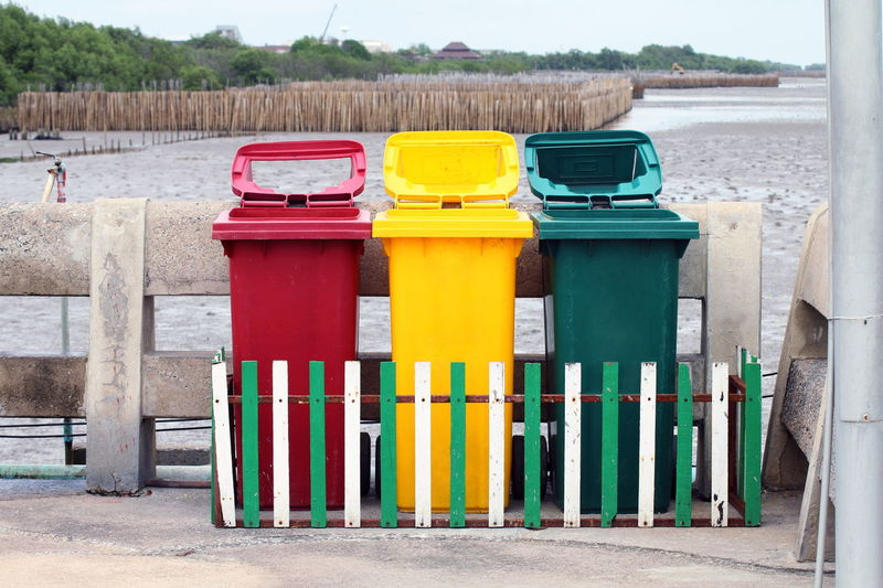 Multi Colored Garbage Bins By Fence Against Field