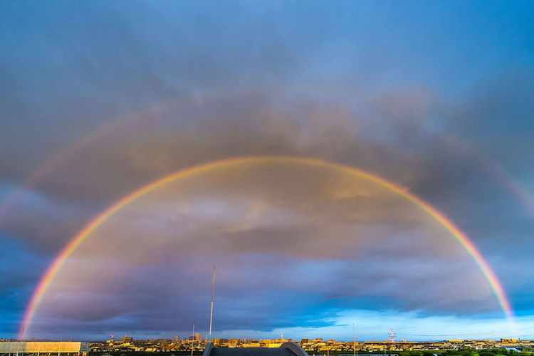 Idyllic shot of rainbow over cityscape against cloudy sky
