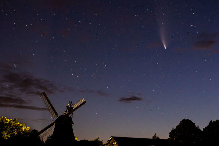 Low angle view of silhouette windmill against sky at night with comet