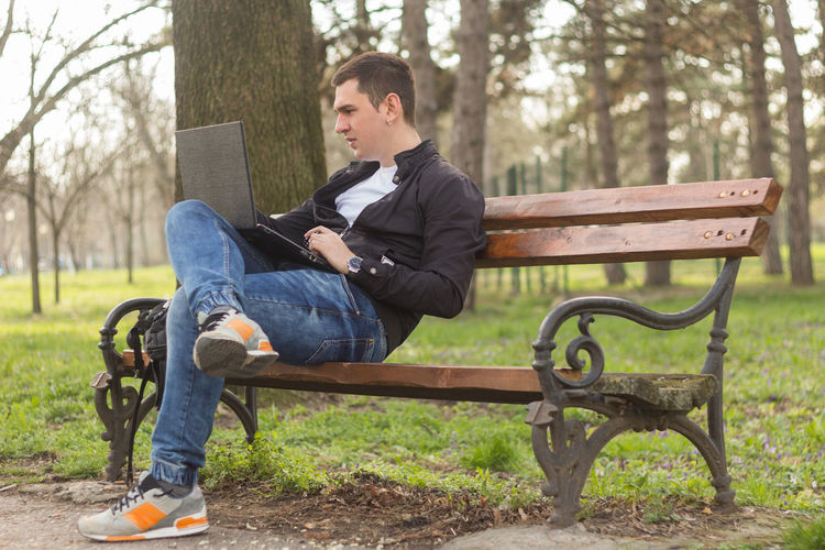 Full length of young man using laptop while sitting on bench in park