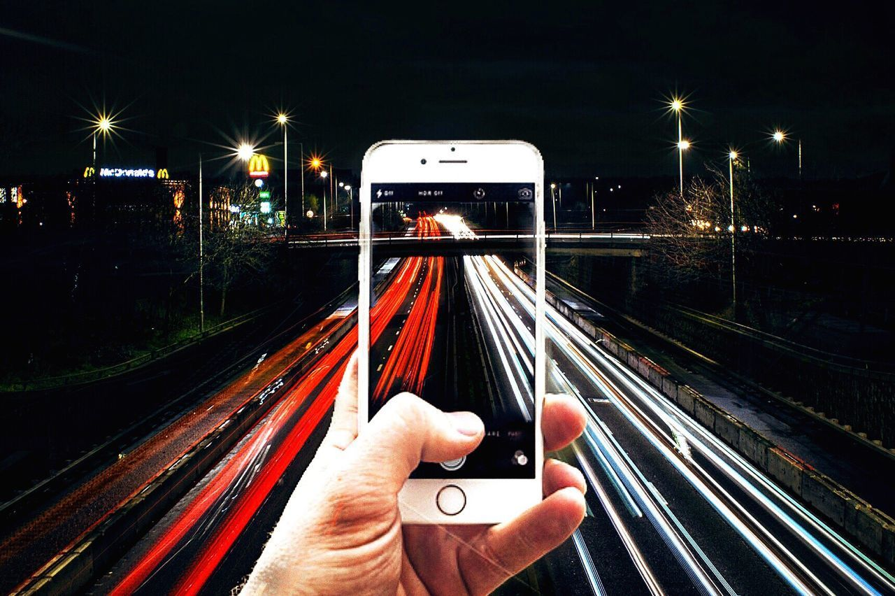 human hand, human body part, transportation, railroad track, personal perspective, human finger, train - vehicle, communication, speed, travel, public transportation, holding, illuminated, real people, mode of transport, one person, night, motion, wireless technology, technology, outdoors, people