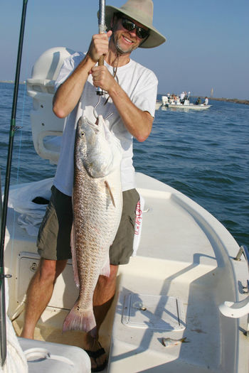 Boat Fisherman Fishing Gulf Of Mexico Hat Red Drum Redfish Saltwater Smiling Sunglasses Texas USA Water