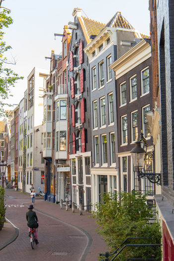 Amsterdam Cyclist Netherlands Architecture Bicycle Building Building Exterior Built Structure Canal Houses City City Life Day Dutch Architecture Dutch Houses Holland Incidental People Land Vehicle Mode Of Transportation Nature One Person Outdoors Plant Real People Residential District Road Street Transportation Window