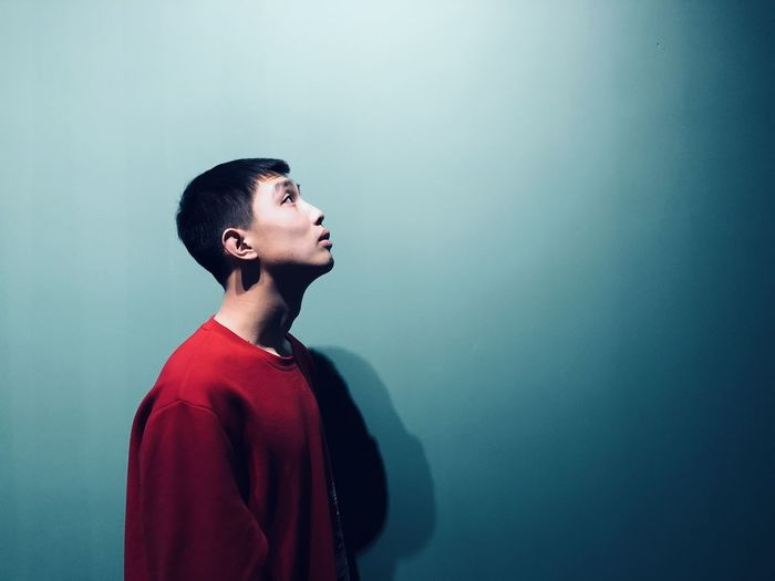 Side view of young man standing against blue background