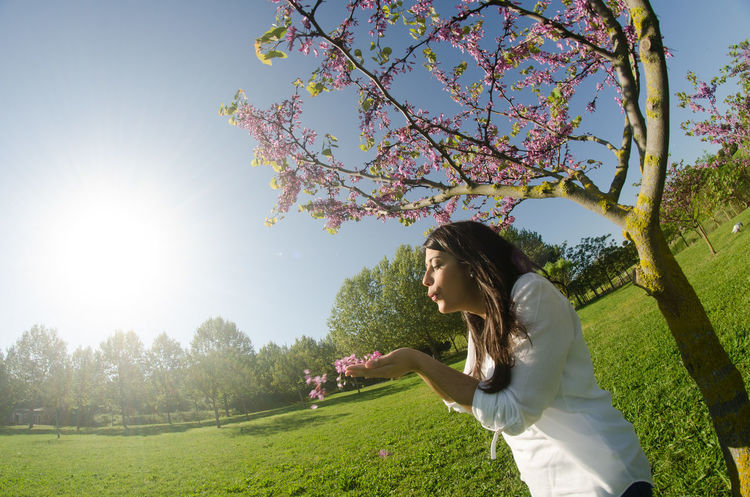 Woman happy with live, enjoy´s the spring the city park Beauty In Nature Casual Clothing Clear Sky Day Field Flower Freshness Grass Growth Leisure Activity Lifestyles Nature One Person Outdoors People Real People Scenics Side View Sky Standing Sunlight Tree Women Young Adult Young Women