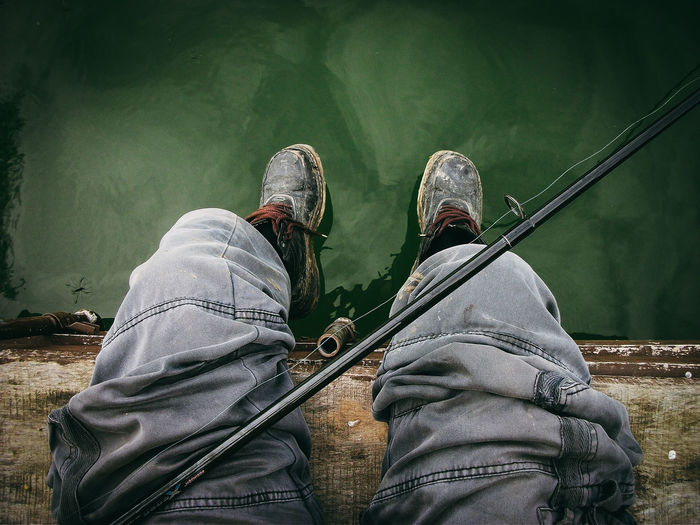Low section of man sitting with fishing rod by lake