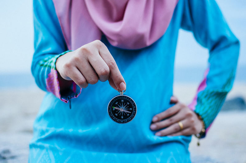 Midsection of woman holding navigational compass at beach against sky
