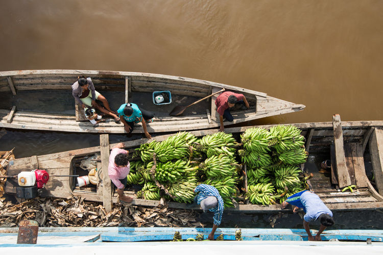 Local Peruvians trading/selling bananas on the Amazon river. Working River Water Fishing Real People Men Day Banana Boat Transportation Peru Third World Wooden Boat Trade Amazon South America Ripe Occupation Fishing Industry High Angle View International Travel Overhead View Green Bananas EyeEmNewHere
