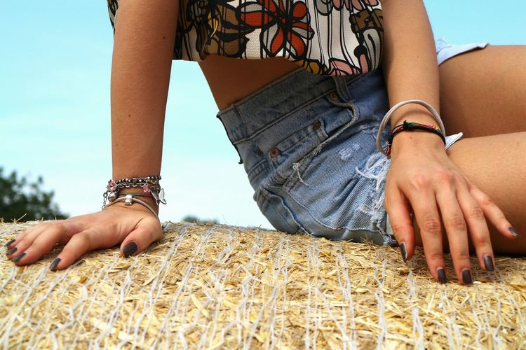 Midsection of young woman sitting on hay