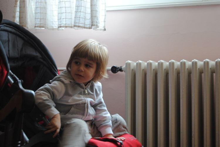 Smiling Boy Sitting In Stroller At Home
