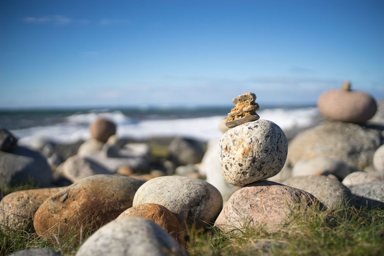 Close-up of pebbles on beach against sky