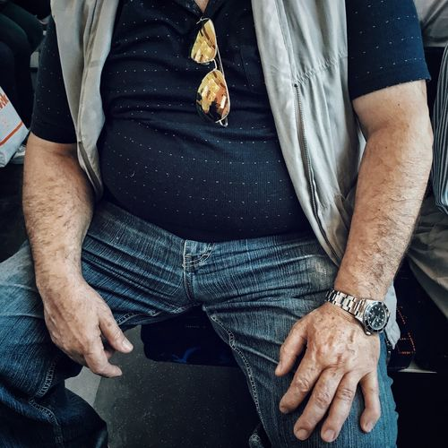 Midsection Of Man Sitting In Train