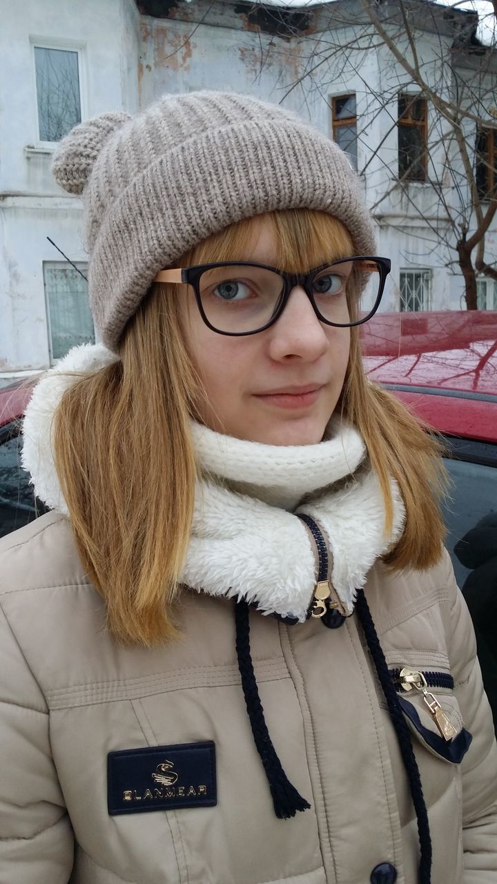 warm clothing, real people, winter, looking at camera, one person, front view, cold temperature, portrait, knit hat, scarf, jacket, lifestyles, day, leisure activity, eyeglasses, young women, outdoors, young adult, close-up, beautiful woman, building exterior