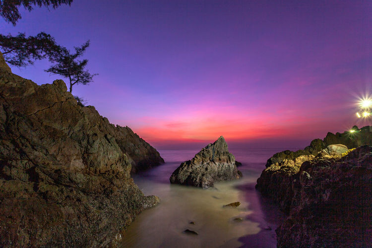 waves hit the big cone shape rock in the middle of stone cape during sunset at banana beach Phuket Cone Cone Shaped Stone, Rocky Mountains Stone Cape, Dracula, Venice Red,sky, Island, Wave, Sea, Edit, Travel, Sunset, Middlw, Banana Beach, Beauty In Nature Scenics - Nature Sky Water Rock Tranquility Tranquil Scene Rock - Object Solid Sunset Nature Idyllic Sea Rock Formation No People Non-urban Scene Land Purple Beach Outdoors