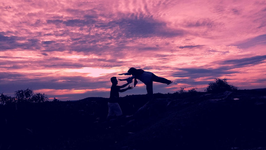 Man catching woman while standing on land against sky during sunset