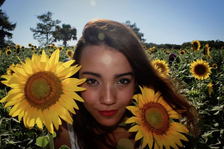 Portrait of woman with sunflowers on field