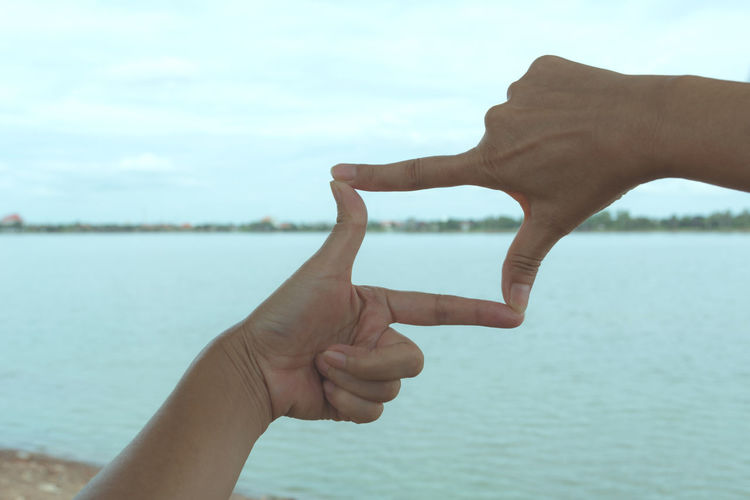 Cropped hands of woman making finger frame against sea