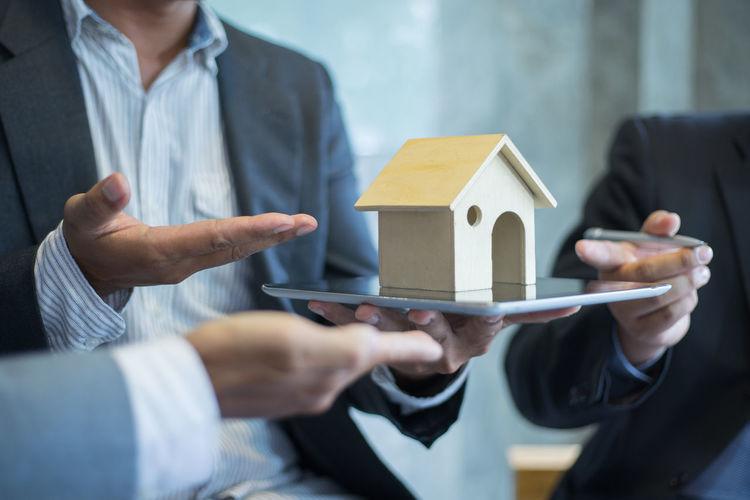 Midsection of businessman holding model house on digital tablet