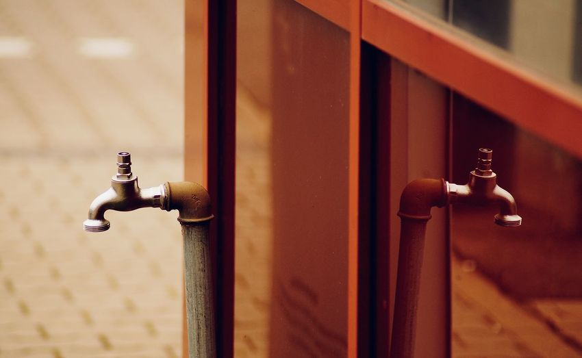 Close-up of faucet against wall