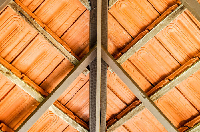 Abstract view from below of terracotta porch roof tiles on house exterior. Burnt Orange Abstract Backgrounds Beams Brown Clay Close-up Construction Design Exterior Full Frame House Low Angle View Outdoors Overhang Pattern Pattern Pieces Porch Roof Rust Color SUPPORT Terracotta Tile View From Below Wooden
