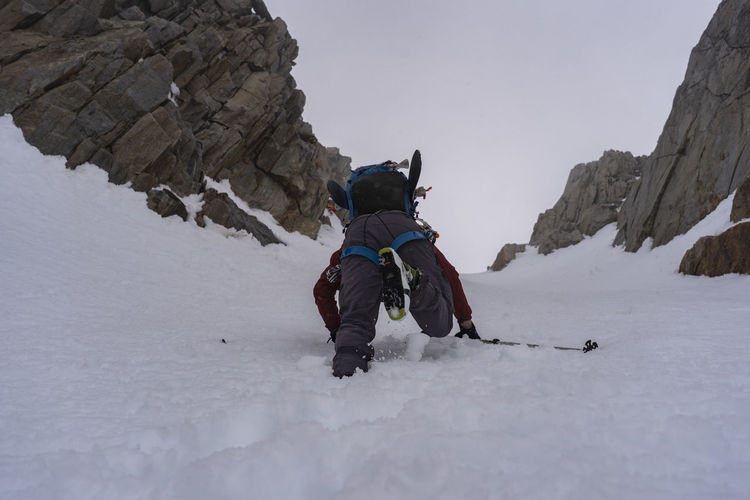 Rear view of people on rock in snow