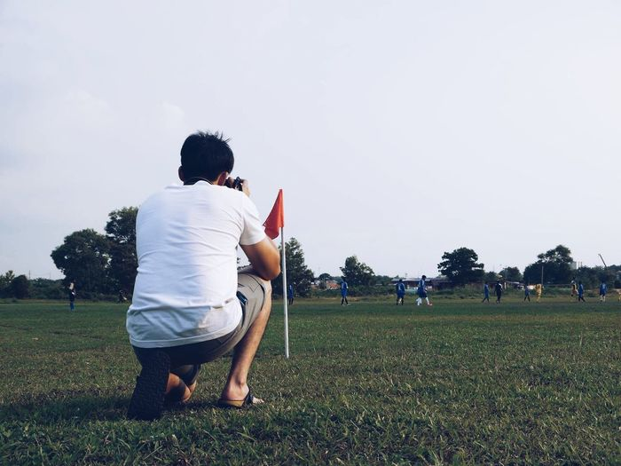 Man photographing while crouching on field against clear sky