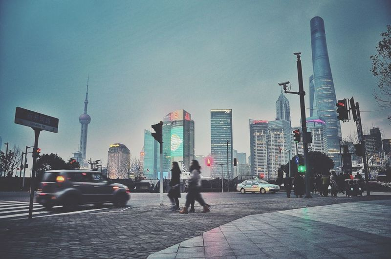 People walking on city street against shanghai tower at dusk