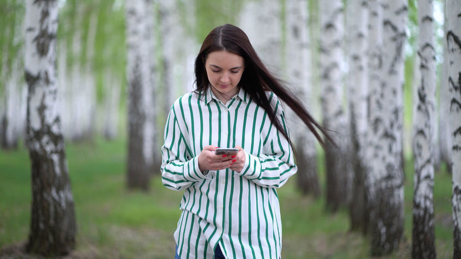 Young woman looking at camera while standing against trees