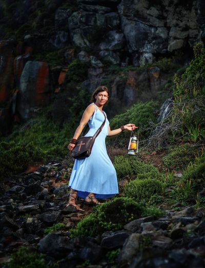 Full length of woman holding lantern while walking on rock in forest