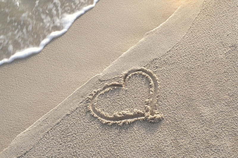 Hand written heart shape in the sand on the beach with beautiful warm sunlight in the morning.
