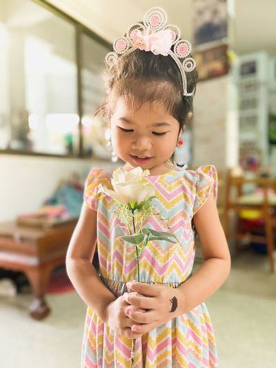 Cute girl holding flower standing at home