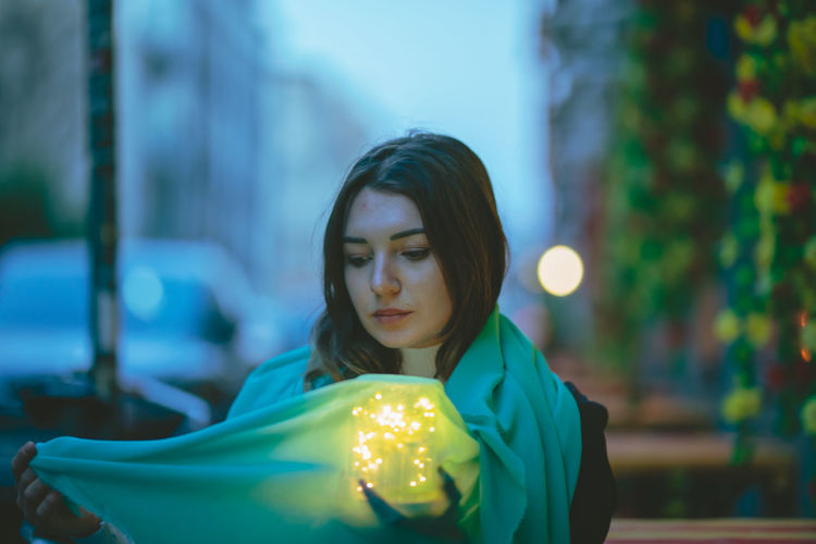 Thoughtful beautiful woman with blue scarf and glowing jar in city at dusk