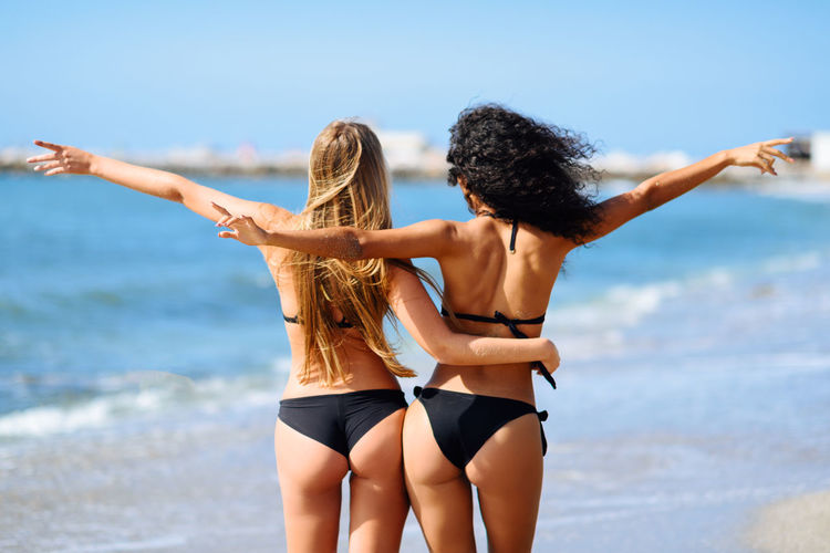 Rear view of two young women with beautiful bodies in bikini having fun on a tropical beach. Girls with open arms. Back Fashion Females Friends Fun Funny Hairstyles Happiness Open Arms Rear View Vacation Time Vacations Beach Bikini Friendship Girls Hairstyle Leisure Activity Sea Sea And Sky Summer Swimwear Women Young Adult Young Women