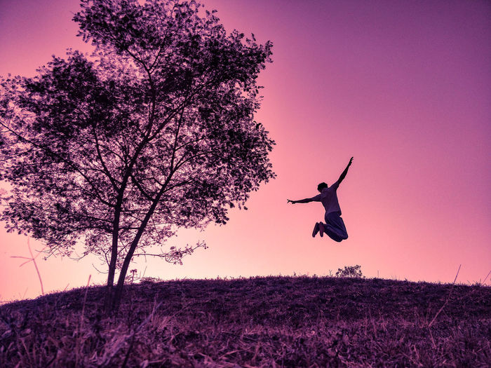 Low angle view of man jumping on field against sky during sunset