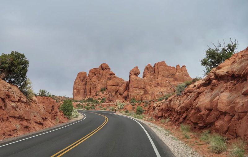 Landscape of road between orange sandstone rock formations in utah