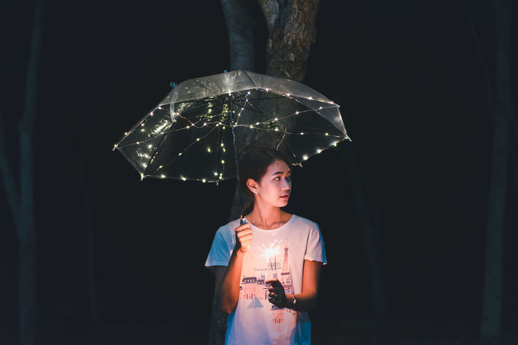 Woman with sparkler holding illuminated umbrella at night