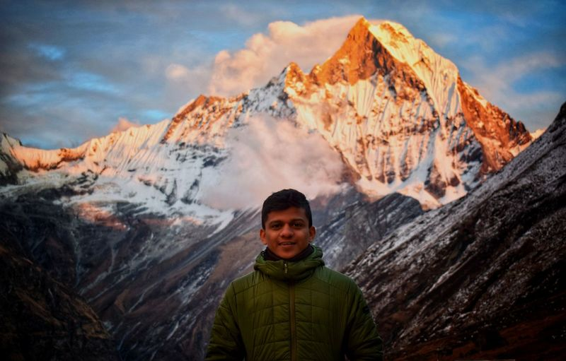 Portrait of man standing against snowcapped mountains