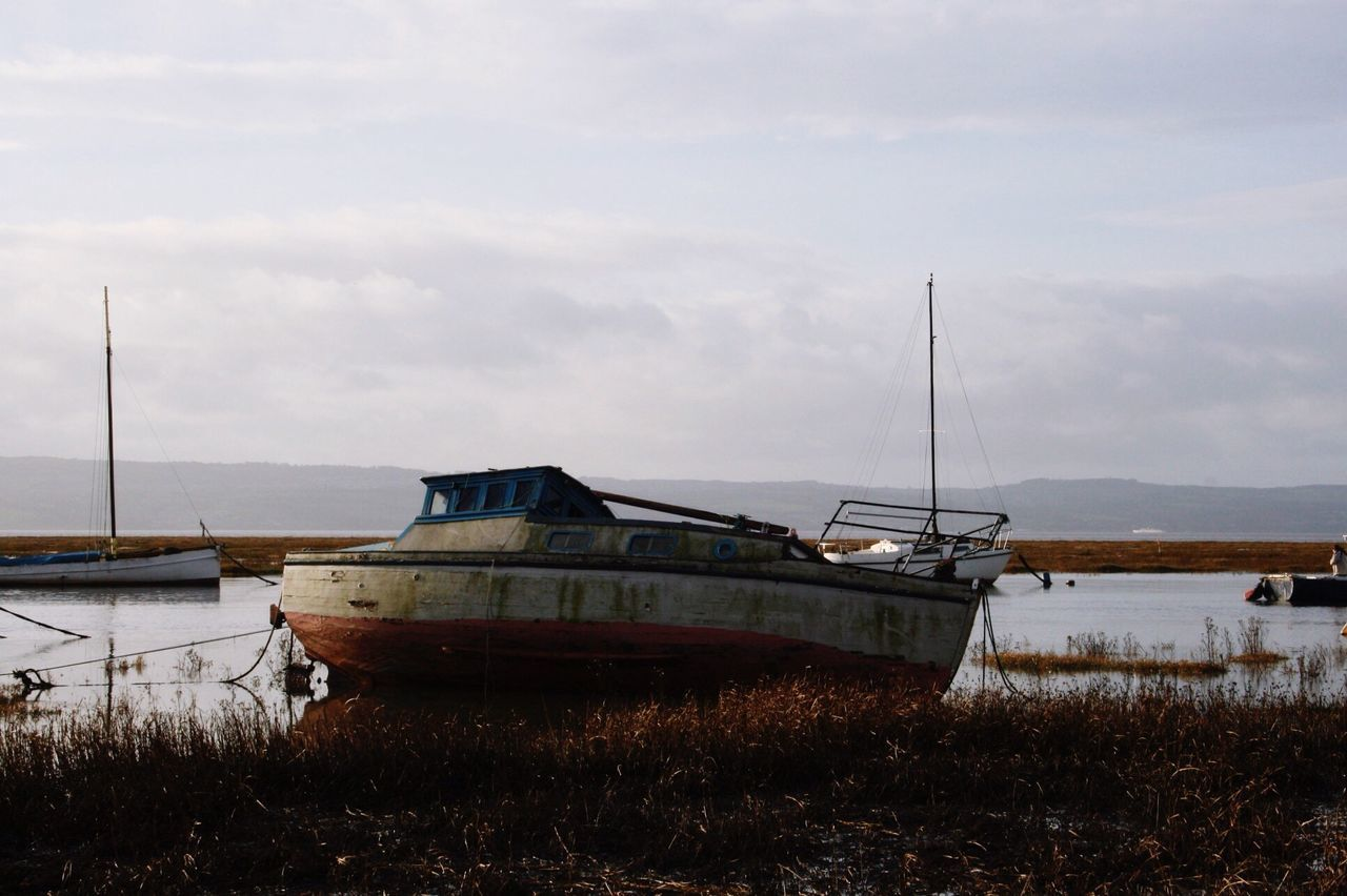 Boat Moored At Riverbank Against Sky
