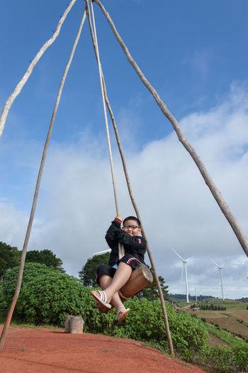 Boy enjoying swing against sky