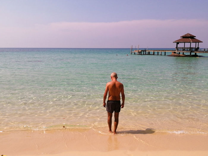 Rear view of shirtless man on beach against sky, in koh kood island, thailand