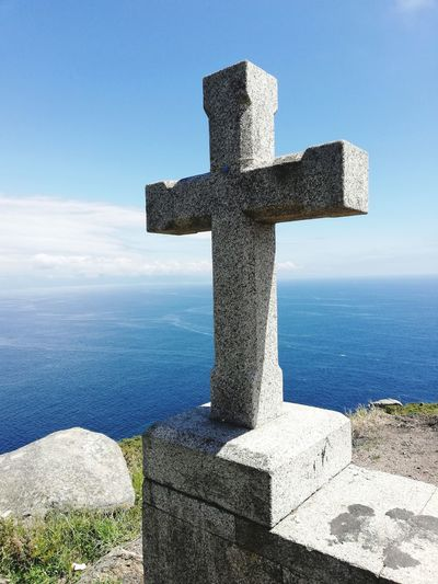 Cross on the headland Finisterre Galicia Cross Spirituality Religion Memorial Sunlight Sea Crucifix Stone Material Tombstone Blue Cross Shape