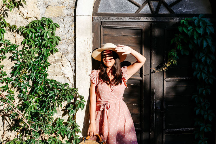 Beautiful young woman in pink dress standing in front of picturesque old house, door, light, shadow.