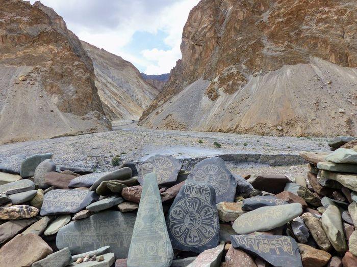 Rocks on mountain against cloudy sky