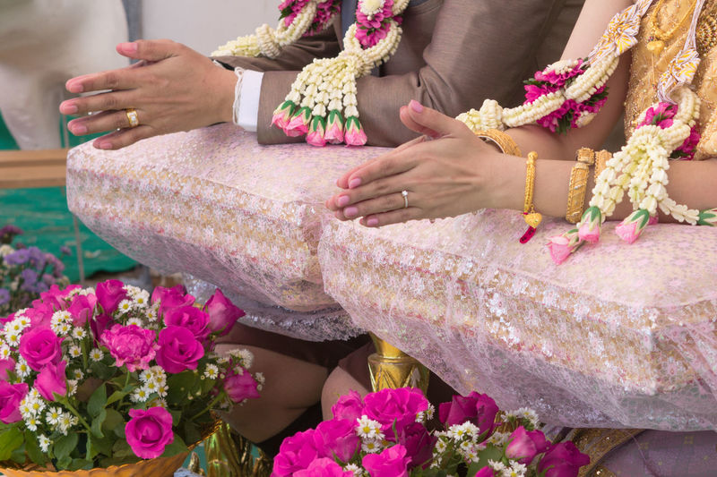 Midsection Of Couple With Hands Clasped During Wedding Ceremony