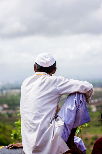 Rear View Of Man Wearing Topi Looking At Field